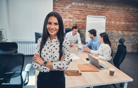 Photo for Happy business posing in modern office at workplace with her colleagues on the background - Royalty Free Image