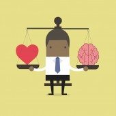 African businessman with Heart and brain on scales