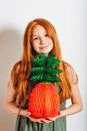 Photo pour Photo de Studio de fille adorable gamin preteen rousse, vêtue d'une robe kakie, jouant à l'ananas de papier - image libre de droit