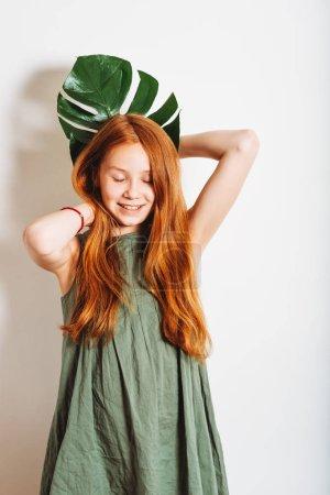 Photo pour Photo de Studio de fille adorable gamin preteen rousse, vêtue d'une robe kakie, jouant avec feuille de Monstera vert exotique - image libre de droit