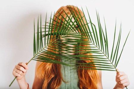 Photo pour Photo de Studio de fille adorable gamin preteen rousse, vêtue d'une robe kakie, se cachant derrière des feuilles de palmier vert exotique - image libre de droit
