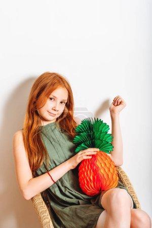 Photo pour Robe coup de Studio de fille adorable gamin preteen roux, vêtu de kaki, jouant à l'ananas de papier, assis sur la chaise en osier - image libre de droit