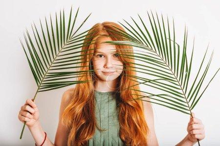 Photo pour Photo de Studio de fille adorable gamin preteen rousse, vêtue d'une robe kakie, jouer avec des feuilles de palmier vert exotique - image libre de droit