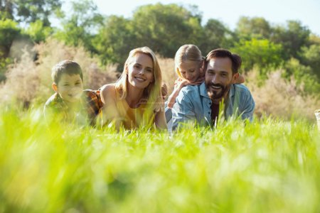 Photo for Relaxing together. Beautiful young mother lying in the grass with her family and smiling - Royalty Free Image