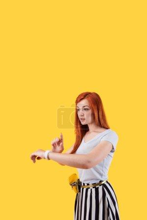 Photo pour Un gadget moderne. Belle femme agréable portant une smartwatch tout en se tenant debout sur fond jaune - image libre de droit