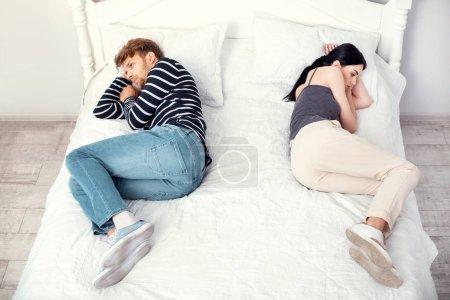 Photo pour Prêt à divorcer. Malheureux couple sympa, allongé sur le lit en pensant à un divorce - image libre de droit