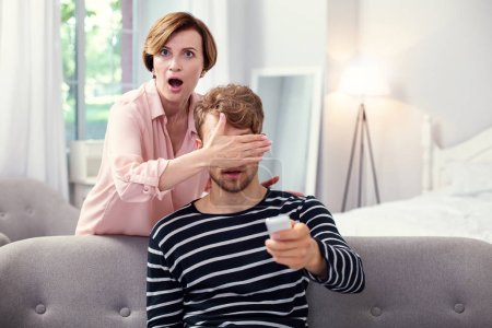 Shocked aged woman covering her sons eyes