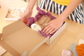 Craftswoman packing little pullovers for children