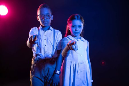 Charming boy and a girl tapping imaginary buttons