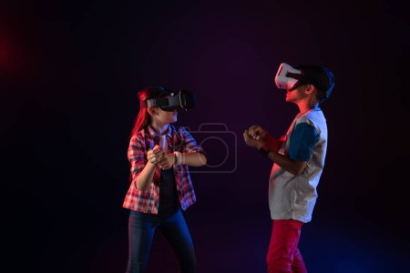 Concentrated little kids wearing VR headsets