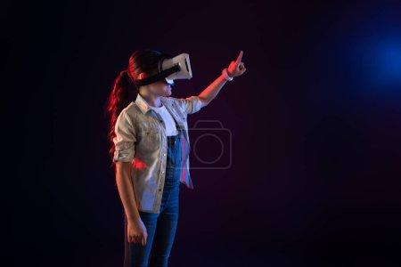 Photo pour Ma récréation. Sourire belle fille portant un casque VR et des images imaginaires touchantes - image libre de droit