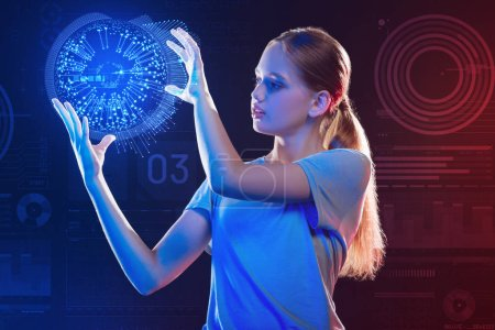 Photo for Careful girl. Attentive clever schoolgirl thoughtfully looking at the realistic hologram while holding it in her hands during the lesson - Royalty Free Image