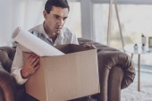 Depressed young man holding a box
