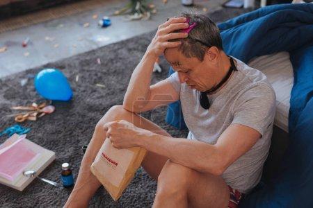 Weary mature man easing hangover