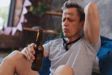 Displeased mature man enjoying alcohol