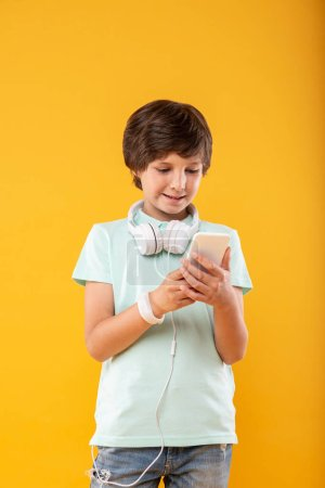 Photo for Cutting-edge technology. Cheerful dark-haired schoolboy using his phone and wearing his headphones - Royalty Free Image