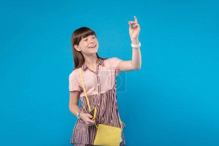 freudiges Schulmädchen mit einer winzigen Nadel in der Hand