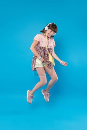 Spaß haben. überglückliche schöne Mädchen springen und Musik hören