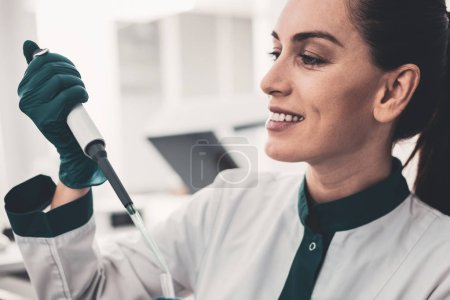 Close up profile of positive professional doctor with pipette