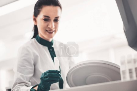 Photo for Checking process. Selective focus of test tube being kept in hand of laboratory assistant during medical investigation - Royalty Free Image