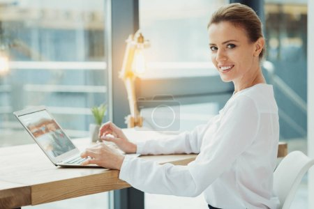 Cheerful boss smiling while working on the laptop