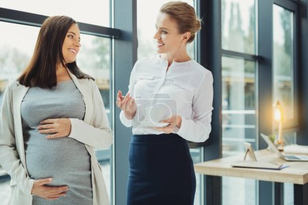 Curious boss asking questions while talking to a pregnant employee