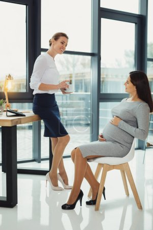 Pregnant woman touching her belly and a kind boss looking at her