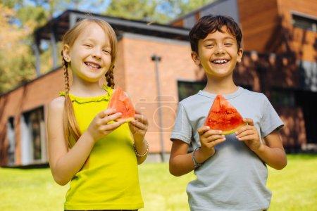Happy children eating a ripe watermelon