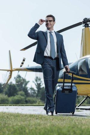 Photo pour Voyageur expérimenté. Un jeune PDG optimiste souriant et ajustant ses lunettes étant arrivé après un vol en hélicoptère et portant une valise - image libre de droit