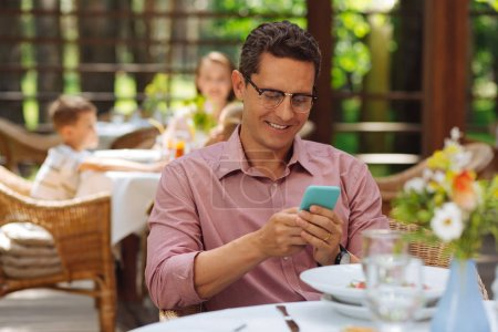 Dark-haired man smiling while reading messages from wife