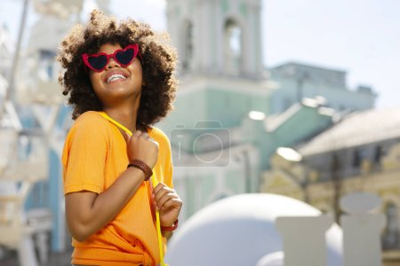 Cheerful curly woman in heart-shaped sunglasses posing in downtown
