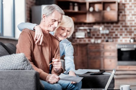 Positive delighted couple staring at computer