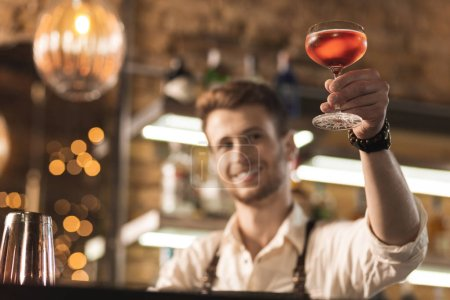 Pleasant young barman checking quality of cocktail