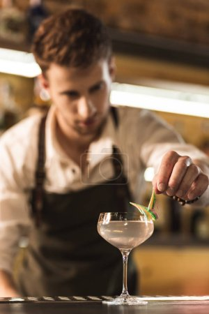 Pleasant young barman adding decoration on glass