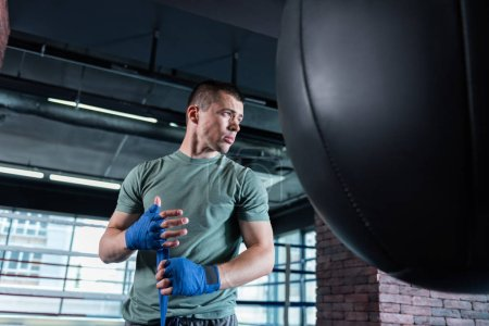 Serious strong sportsman training hard in gym