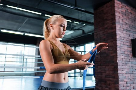Blonde-haired fitness trainer rolling her hands in wrist wraps