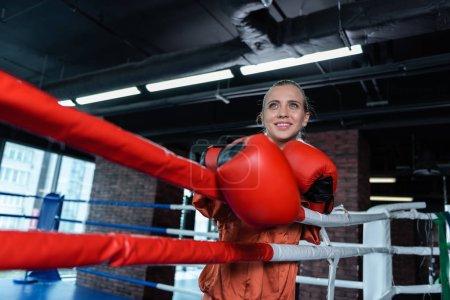 Photo pour Temps libre. Rayonnant femme athlétique formation en ring de boxe tout en ayant un temps libre du travail - image libre de droit