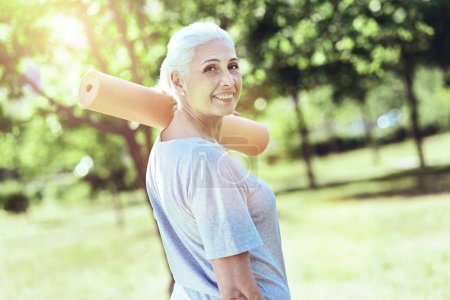 Happy aged woman standing with a yoga mat