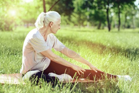 Calm exercise. Kind relaxed elderly woman slowly exercising in a quiet park