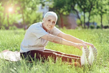 Active pensioner trying to touch her feet