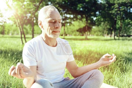 Calm pensioner smiling while meditating