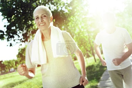 Happy elderly woman running faster than her husband