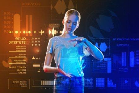 Photo pour Tenue d'hologrammes. Calme curieux adolescent intelligent tenant un hologramme rond réaliste et en regardant pensivement - image libre de droit