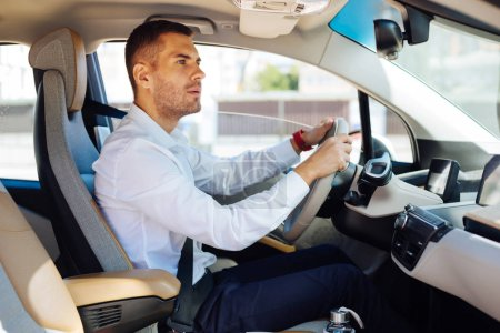 Photo for Heavy traffic. Careful male drive looking into the mirror while driving in his car - Royalty Free Image