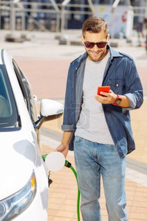 Joyful positive man fuelling his car