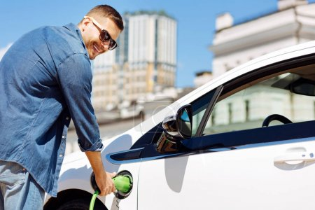Fuel refilling. Joyful handsome man holding a fuel nozzle while refilling his car