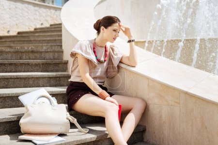 Sad young woman sitting on the stairs