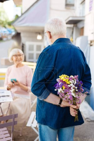 Appealing senior man bringing bouquet