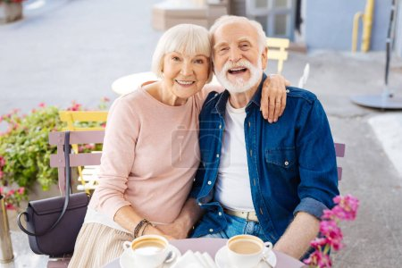 Photo for Never boring. Smiling senior couple sitting at cafe and looking at camera - Royalty Free Image