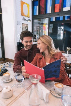 Cheerful jolly couple organizing date at cafe